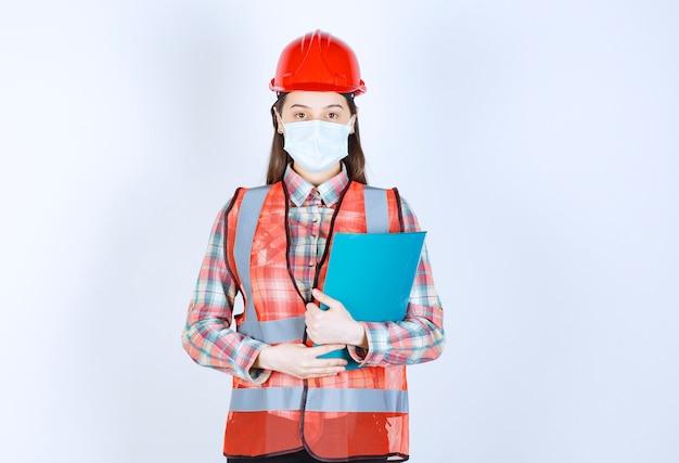 Żeński inżynier budowlany w masce ochronnej i czerwonym kasku, trzymający niebieski folder