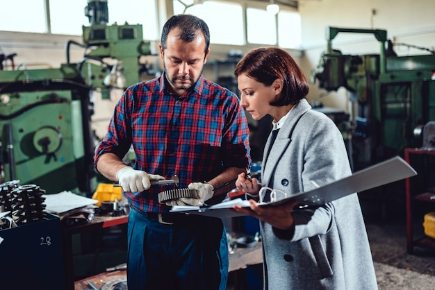 Żeński inżynier dyskutuje z mechanika mienia cogwheel i analizuje projekt