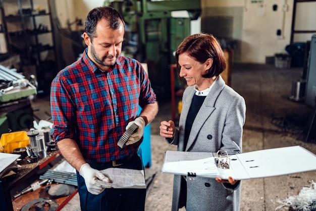 Żeński inżynier konsultuje z mechanika mienia cogwheel i analizuje projekt