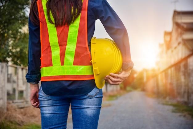 Żeński inżynier trzyma hardhat bezpieczeństwo stoi plenerowego miejsce pracy