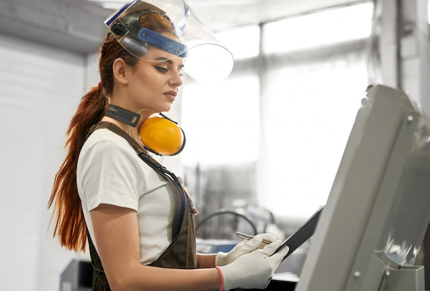 Żeński inżynier w ochronnych ubraniach pracuje na fabryce.