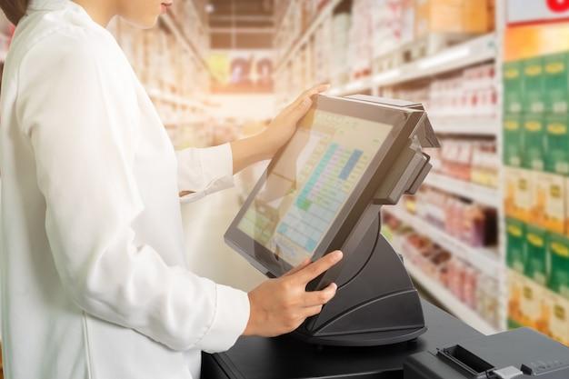Żeński kasjer personel stoi i pracuje z maszyną pos lub punktu sprzedaży przy kontuarem w supermarkecie.