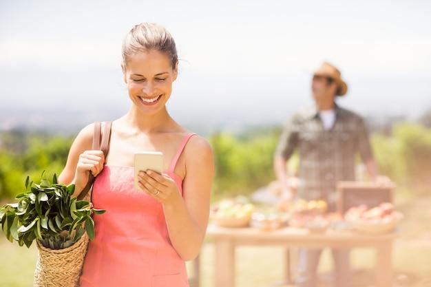 Żeński klient używa telefon komórkowego przed warzywo kramem