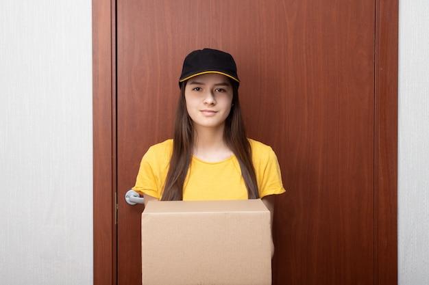 Żeński kurier w mundurze stoi przy drzwiach z pudełkiem