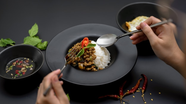 Żeński łasowanie mieszam smażącą mieloną wieprzowinę z basilem na czerń stole w tajlandzkiej restauraci (pad ka prao)