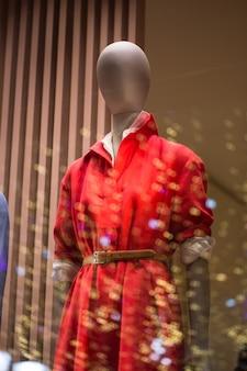 Żeński manekin w czerwonej bluzie w oknie sklepu