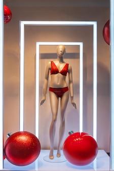 Żeński manekin w czerwonym kostiumie kąpielowym w oknie butiku i dwie ogromne czerwone bombki świąteczne, wyprzedaże noworoczne