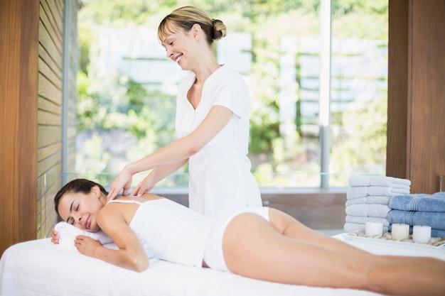 Żeński masażysta masuje pięknej kobiety przy zdrojem
