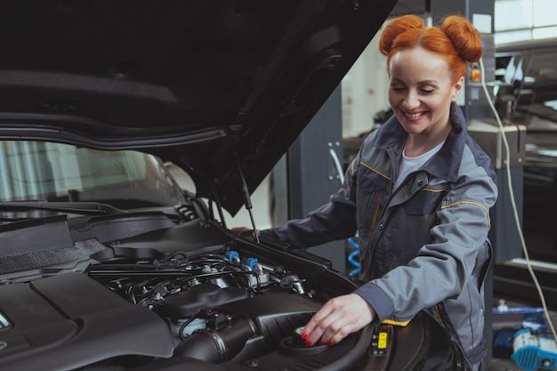 Żeński mechanik pracuje przy samochodową stacją obsługi