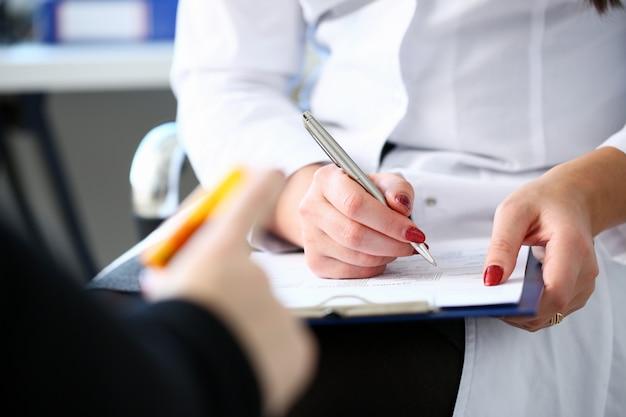 Żeński medycyny lekarki ręki chwyta słój pigułki i pisze recepcie pacjent przy stołem roboczym. panaceum i ratowanie życia, przepisywanie leczenia, legalna koncepcja apteki. pusty formularz gotowy do użycia