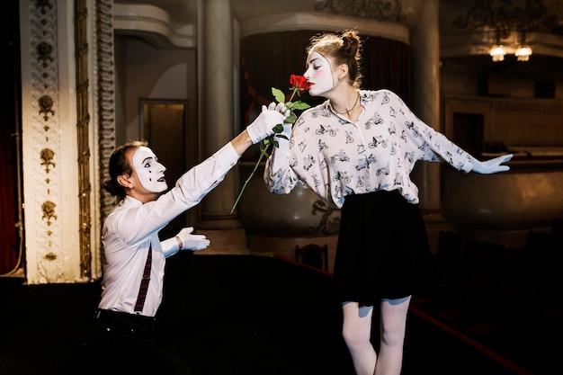 Żeński mima artysta wącha czerwieni róży dawać męskim mimem na scenie