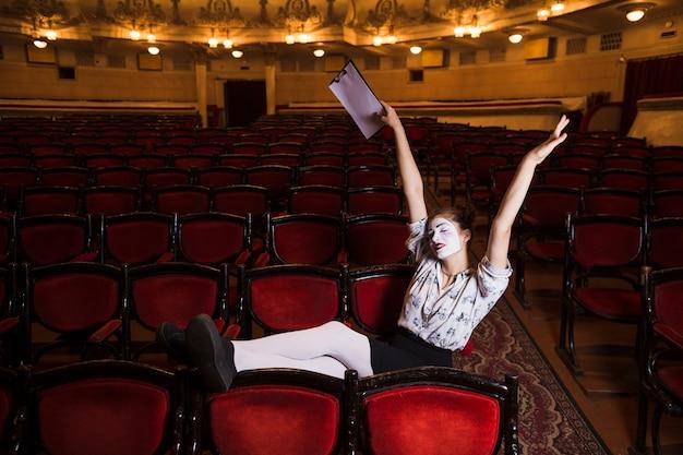 Żeński mima obsiadanie na czerwonym krześle rozciąga ona ręki