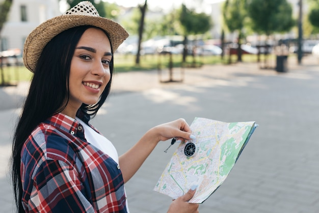 Żeński młody podróżnik trzyma nawigacyjnego kompas i mapę podczas gdy patrzejący kamerę