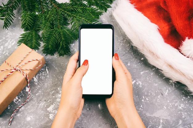 Żeński nabywca robi rozkazowi przy ekranem smartphone z kopii przestrzenią. świąteczne zakupy online. kobieta kupuje prezenty na boże narodzenie. sprzedaż ferii zimowych. stonowanych