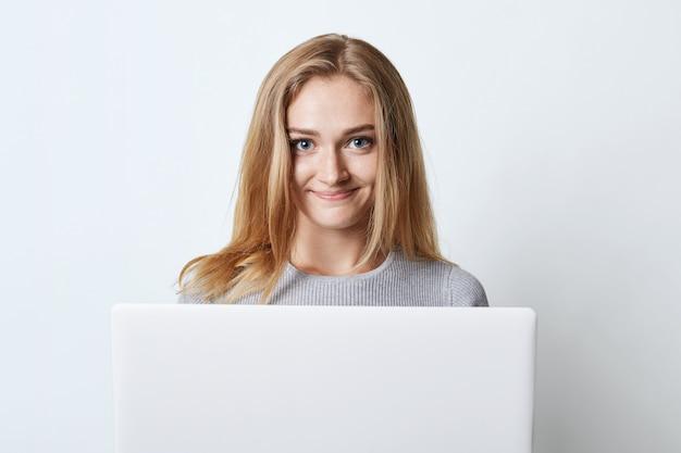 Żeński nastolatek pracuje przy komputerem, preapring dla klas lub surfuje ogólnospołeczne sieci, patrzeje z szczęśliwym wyrażeniem w kamerę odizolowywającą na bielu. modelki za pomocą nowoczesnego gadżetu