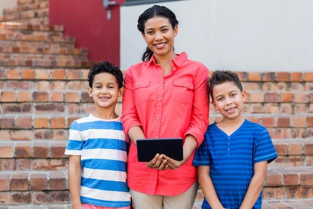 Żeński nauczyciel z uczniami trzyma cyfrową pastylkę
