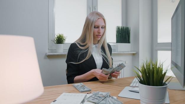 Żeński odliczający pieniądze przy biurowym miejscem pracy. piękna młoda blond kobieta w garnituru obsiadaniu w biurze przy lekkim drewnianym biurkiem z komputerem koncentruje się na odliczającym ampuła stosie gotówka w rękach