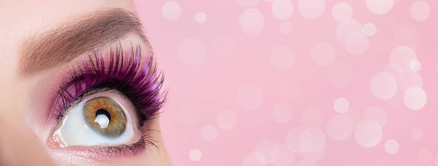 Żeński oka zakończenie up na różowym tle z bokeh i kopii przestrzenią