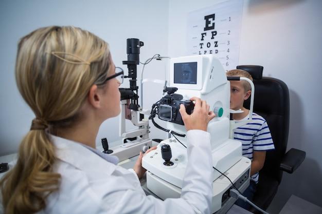 Żeński okulista egzamininuje młodego pacjenta na coreometry