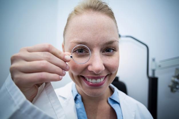 Żeński okulista patrzeje przez powiększać - szkło