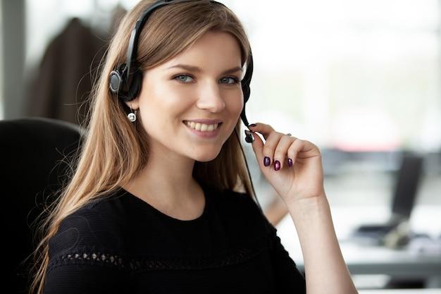 Żeński operator obsługi klienta z zestawem słuchawkowym i uśmiechnięty.
