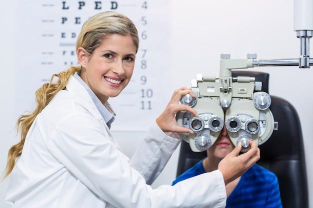 Żeński optometrist egzamininuje młodego pacjenta na phoropter
