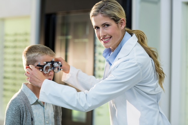 Żeński optometrist egzamininuje młodego pacjenta z phoropter