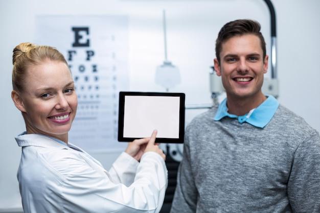 Żeński optometrist ma dyskusję z pacjentem na cyfrowej pastylce
