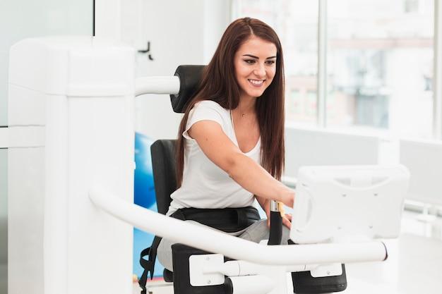 Żeński pacjent używa medyczną maszynę