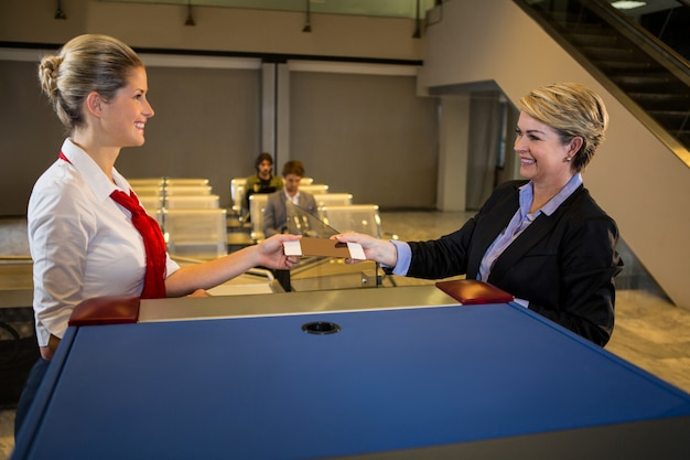 Żeński personel daje abordaż przepustce bizneswoman przy kontuarem