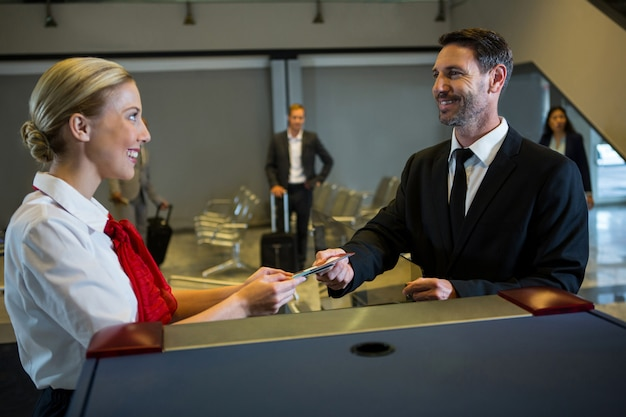 Żeński personel daje kartę pokładową do biznesmena