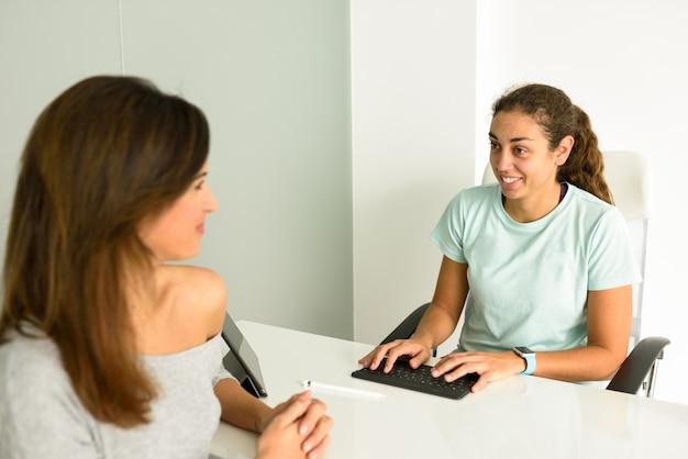 Żeński physiotherapist wyjaśnia diagnozę jej kobieta pacjent.
