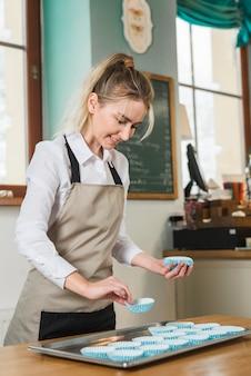 Żeński piekarz stawia błękitną babeczki skrzynkę w stali nierdzewnej tacy