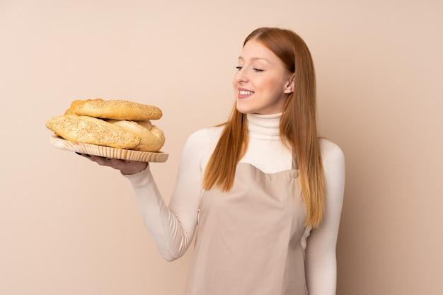 Żeński piekarz trzyma stół z kilka chlebami z szczęśliwym wyrażeniem