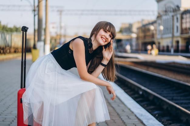 Żeński podróżnik z czerwonym walizki czekania pociągiem na staci kolejowej