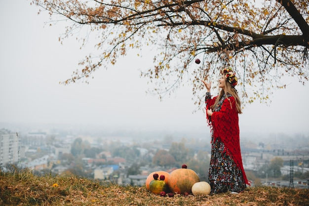 Żeński portret. urocza kobieta w ciąży w długiej sukni i czerwieni s