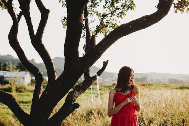 Żeński portret. urocza kobieta w czerwonej sukience stoi pod ol