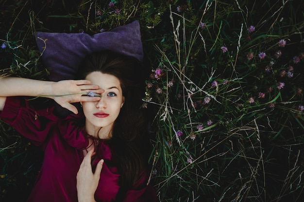 Żeński portret. urocza kobieta w fioletowej koszuli leży na gree