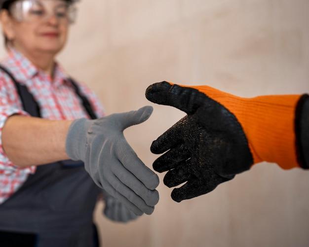 Żeński pracownik budowlany daje uścisk dłoni hełm i rękawiczki