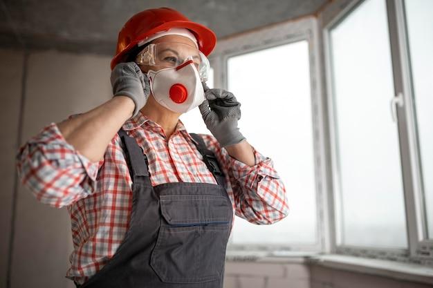 Żeński pracownik budowlany jest ubranym maskę z hełmem i słuchawkami