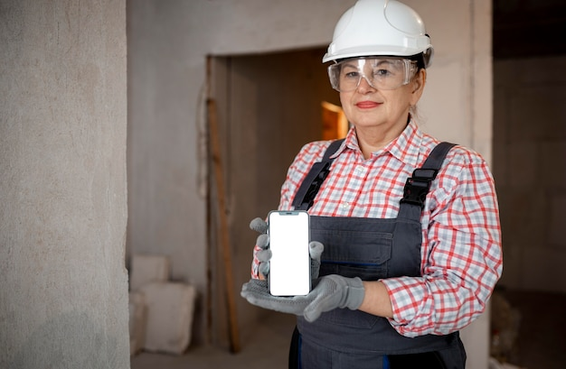 Żeński pracownik budowlany trzymając smartfon z hełmem