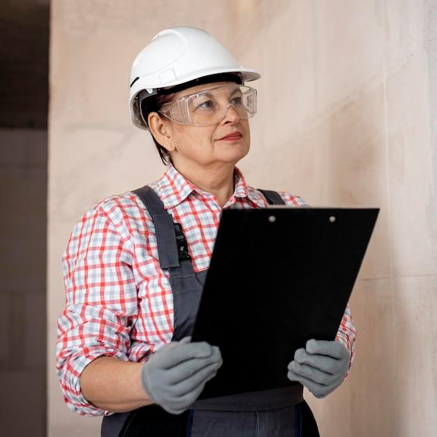 Żeński pracownik budowlany z hełmem i schowkiem