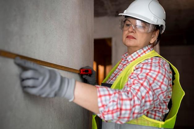 Żeński pracownik budowlany z hełmem i taśmą mierniczą