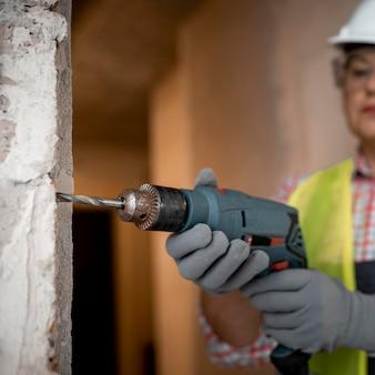 Żeński pracownik budowlany z hełmem i wiertarką elektryczną