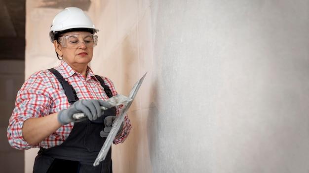 Żeński pracownik budowlany z kaskiem wygładzanie ściany
