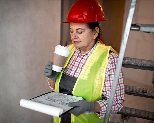 Żeński pracownik budowlany z kawą i planem
