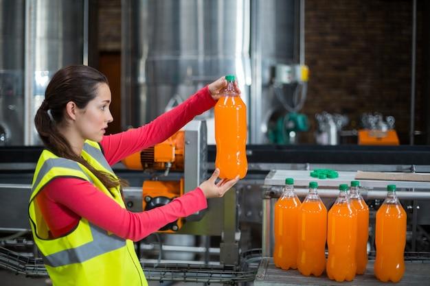 Żeński pracownik fabryczny egzamininuje butelkę sok