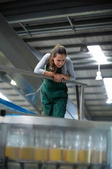 Żeński pracownik fabryczny sprawdza linię produkcyjną