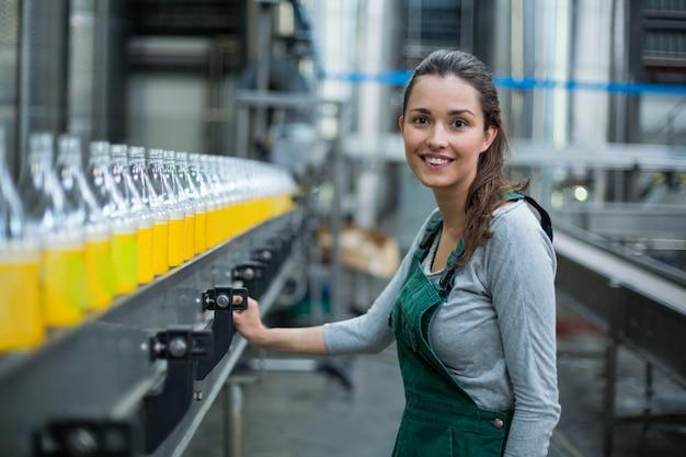 Żeński pracownik fabryczny stoi blisko linii produkcyjnej