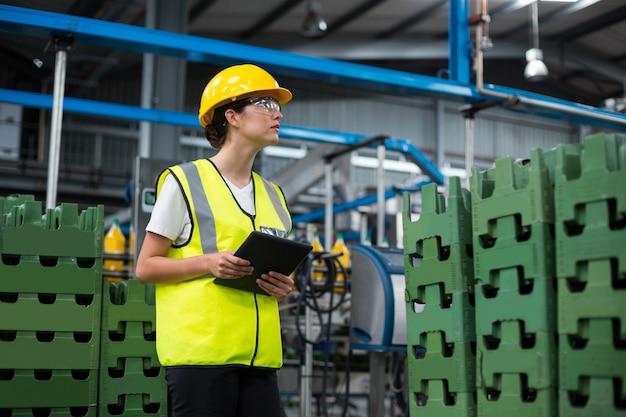 Żeński pracownik fabryczny utrzymuje rejestr na cyfrowej pastylce